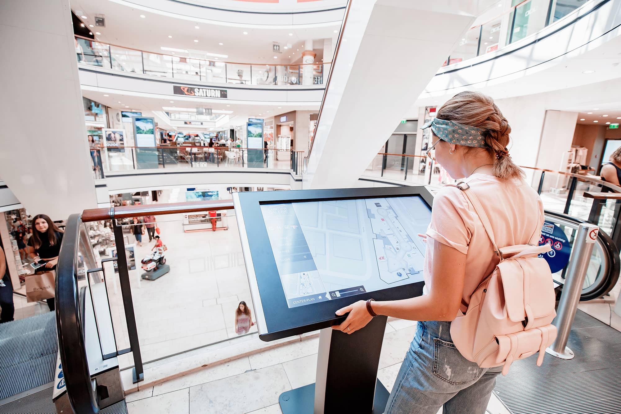 Frau in Geschäft an Touch-Table von commalive